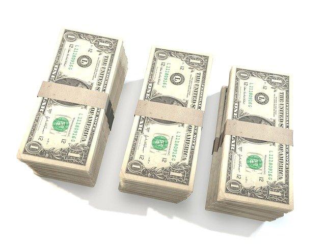 tři hromádky dolarů